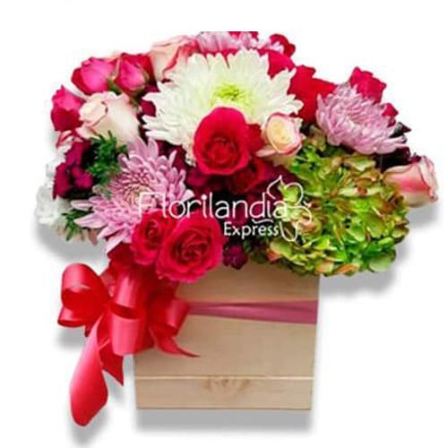 Hermoso arreglo de flores en base tipo guacal, con hortencias, rosas, margaritas, pompones y follajes.