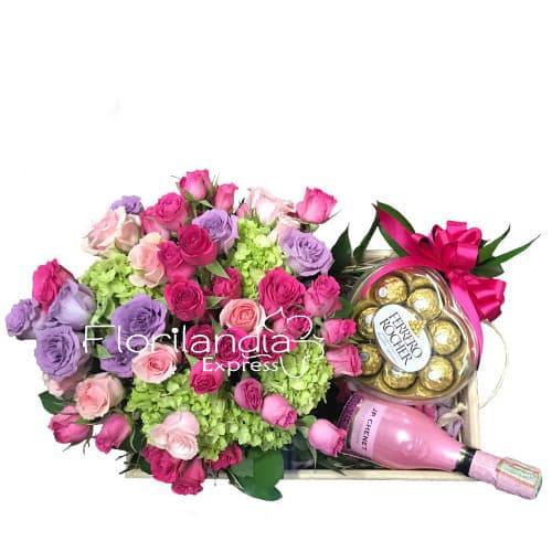 Hermoso arreglo floral con hortencias y minirosas, en base de guacal. Acompañado por una botella de mini champaña JP chenet y unos chocolates ferrero