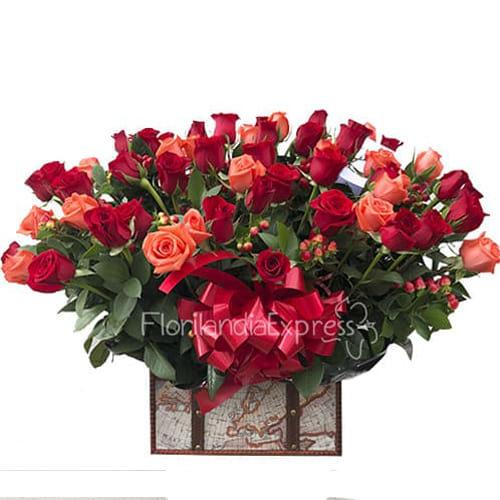 Cofre por 50 rosas salmon y rojas con follajes verdes.